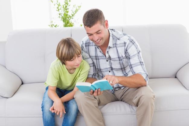 Père, lecture d'histoire pour garçon sur le canapé