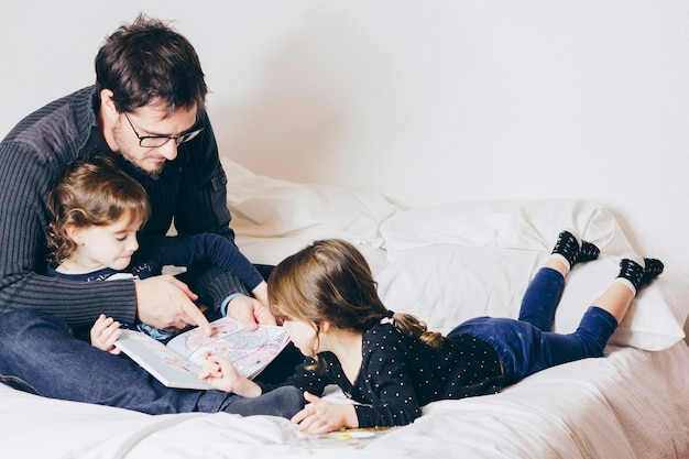Père, lecture de livre avec des filles mignonnes