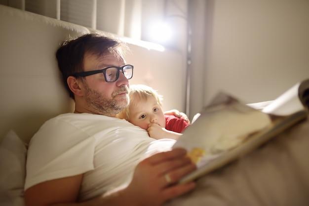 Père lire des histoires au coucher à l'enfant. papa endormir son fils