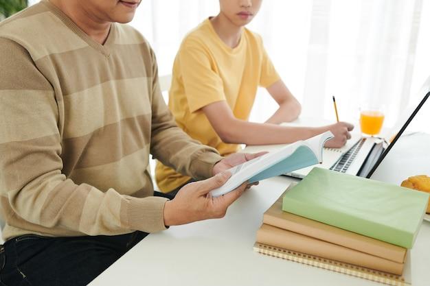 Père lisant un livre d'étudiants et expliquant un sujet difficile à son fils adolescent