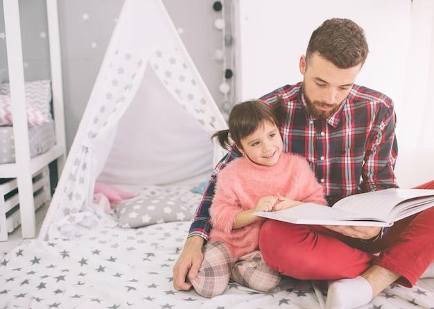 Père lisant un livre à sa fille allongé sur le sol dans la chambre. mignonne petite fille et son beau jeune papa jouent ensemble dans la chambre d'enfant.