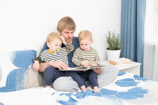 Père lisant un livre à ses fils jumeaux sur le lit à la maison passer du temps ensemble