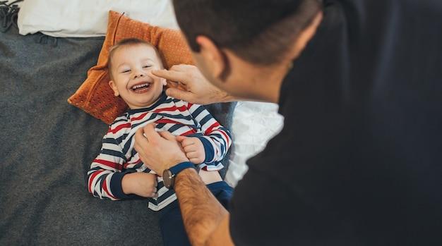 Père ludique chatouille son petit fils qui est allongé sur le canapé et sourit joyeusement