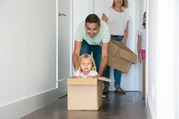 Père ludique poussant une boîte en carton avec une jolie fille à l'intérieur