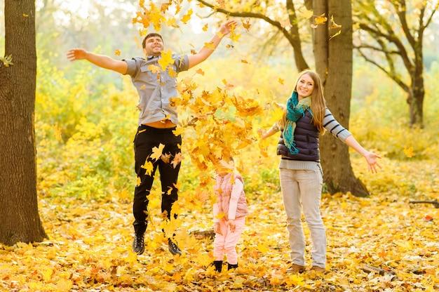 Le père maman et leur fille jettent des feuilles d'automne dans le ciel.