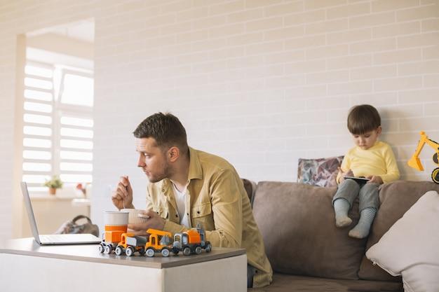Père mangeant et travaillant à domicile