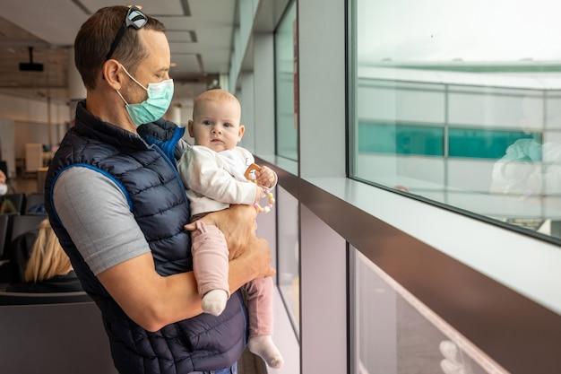 Père en masque médical et sa fille en attente d'un embarquement dans un avion à l'aéroport