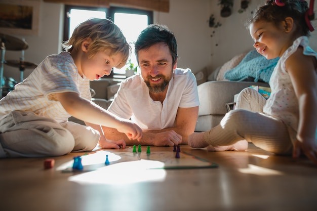 Père mature avec deux petits enfants se reposant à l'intérieur à la maison en jouant à des jeux de société
