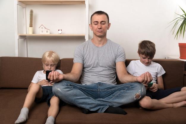 Père médite pendant que les enfants utilisent des gadgets. papa a calmé ses fils et les a détendus.