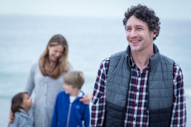 Père et mère debout avec des enfants à la plage
