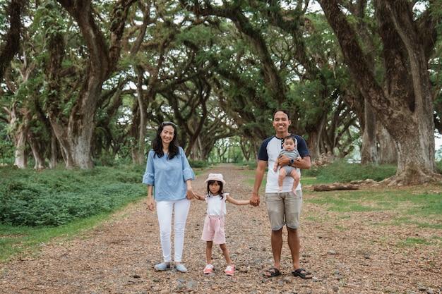 Père, mère et deux enfants marchent ensemble