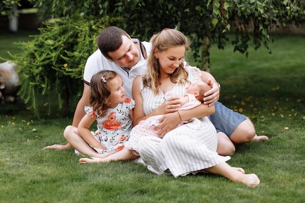 Père, mère et deux enfants, petite fille et petite fille sur l'herbe le jour d'été.