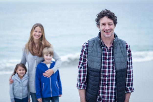 Père avec mère et enfants à la plage