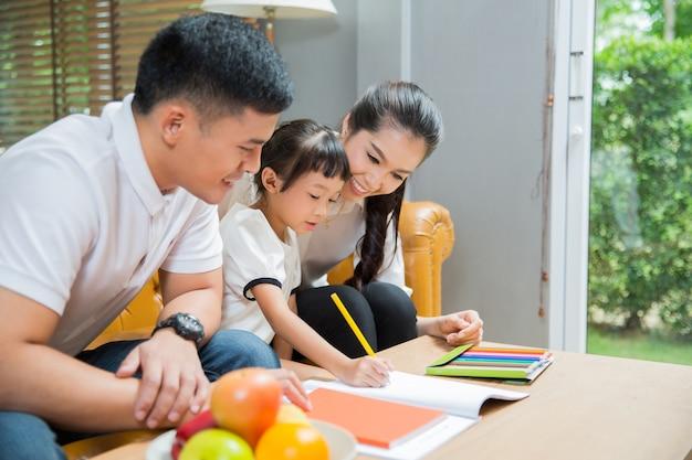 Père et mère enseigner aux enfants à faire leurs devoirs à la maison