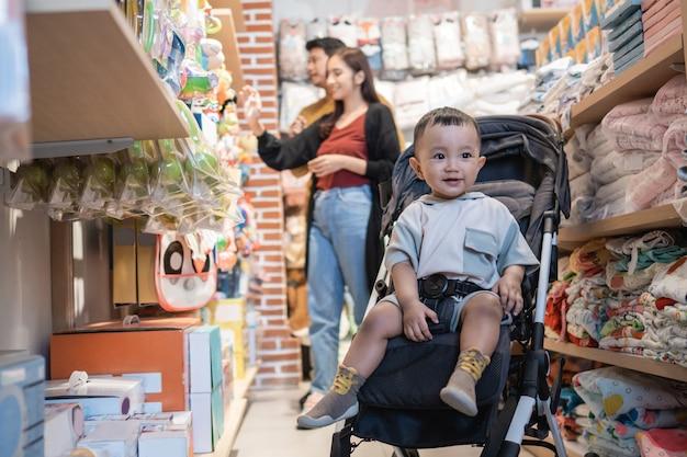 Père et mère faisant leurs courses au magasin pour bébés avec leur fils dans la poussette
