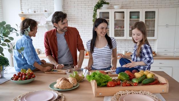 Père de mère de famille végétalienne et deux petits enfants excités cuisinant ensemble dans la cuisine à la maison ils