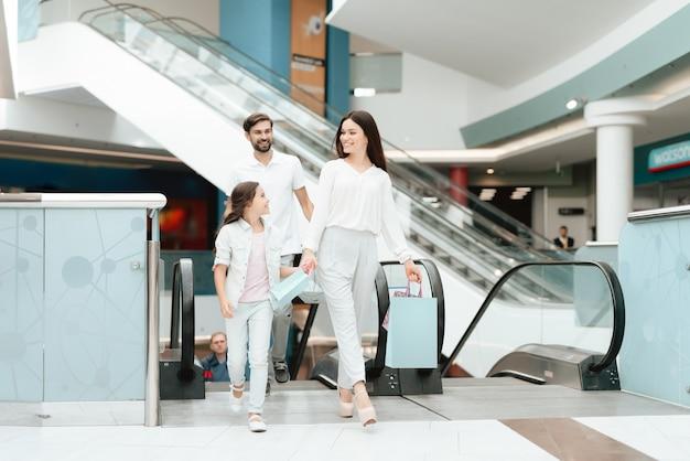 Père, mère et fille avec des sacs à provisions.