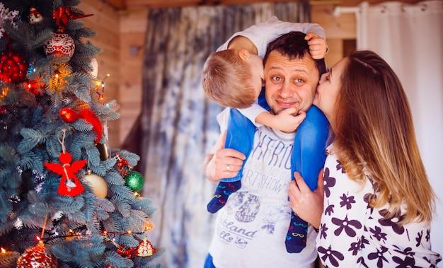 Le père, la mère et le fils debout près de l'arbre de noël