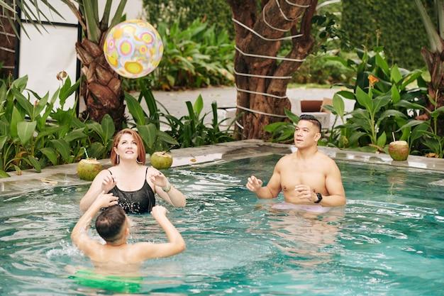 Père, mère et fils jouant avec ballon gonflable dans la piscine de la station thermale
