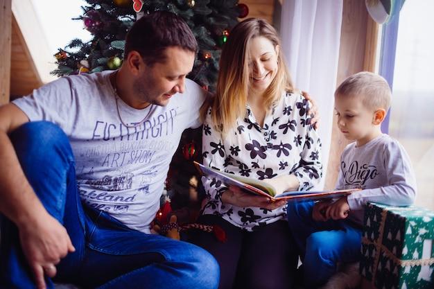 Le père, la mère et le fils lisant un livre