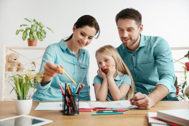 Père, mère et leur fille sourient en passant du temps ensemble. une journée en famille. jeune couple heureux avec enfant apprend à dessiner. concept d'éducation, d'étude et de partage des connaissances.