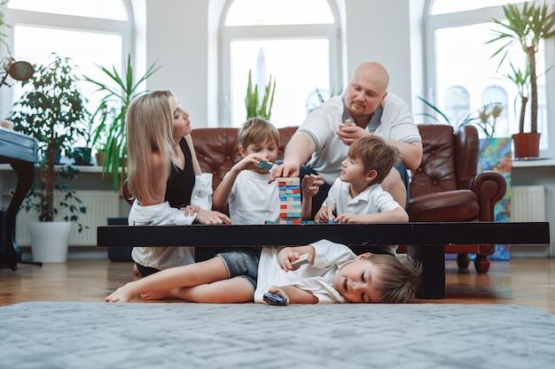 Père et mère avec leurs enfants apprenant à jouer ensemble au jeu de jenga. portrait de garçons joyeux et de leurs parents dans le salon.
