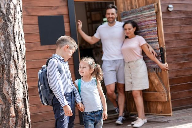 Un père et une mère ont rassemblé leurs deux enfants pour l'école, qui ont attendu poliment le bus scolaire dans la rue, une fille et un garçon se tiennent la main et parlent.
