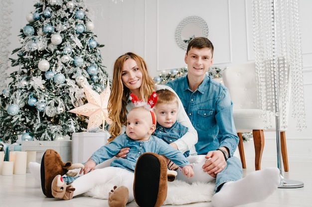 Le père, la mère tient le petit fils et la fille près de l'arbre de noël.