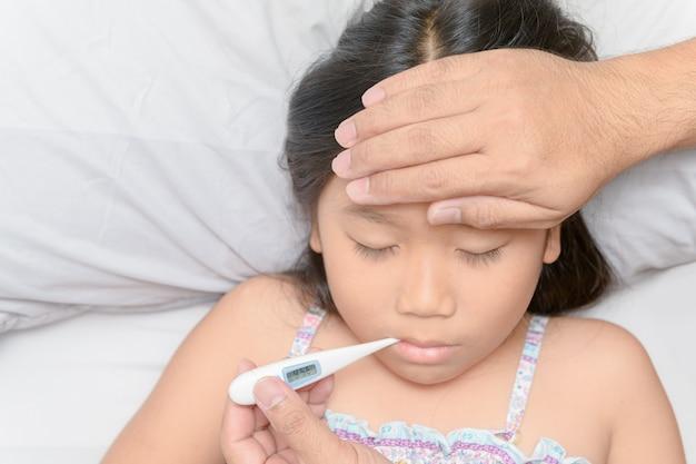 Père mesurant la température d'un enfant malade.