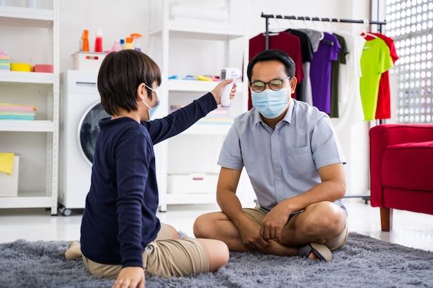 Le père met un masque médical pour son fils dans la quarantaine et l'épidémie de coronavirus à domicile