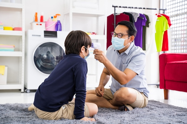 Le père met le masque médical de son fils dans la quarantaine et l'épidémie de coronavirus à domicile