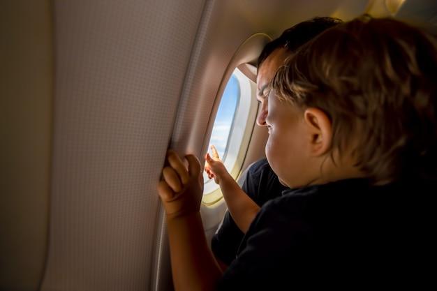 Père et mignon petit ciel au hublot. concept de premier vol, voyageant avec des enfants.