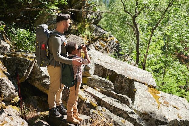Père montrant la belle nature à son fils pendant qu'il regarde à travers les jumelles, ils sont dans la forêt