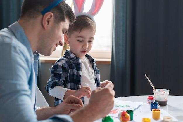 Père montrant à son fils comment peindre des oeufs de pâques