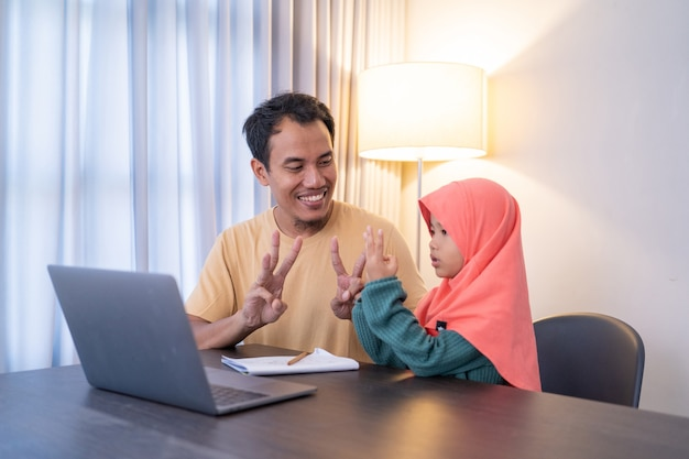 Un père musulman enseigne à sa fille pendant la scolarité à domicile le soir