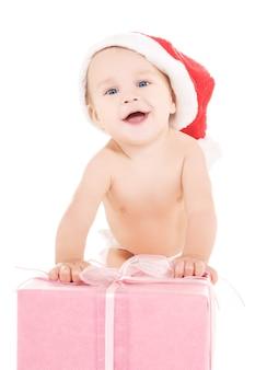 Père noël aide bébé avec cadeau de noël sur mur blanc