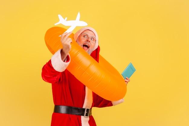 Père noël avec anneau en caoutchouc, passeport et avion en papier, heureux de voyager pendant les vacances de noël
