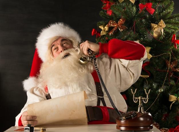 Père noël appelant avec téléphone vintage en lisant une lettre de vieux rouleau