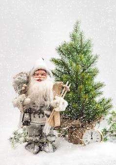 Père noël avec arbre de noël dans la neige. décoration d'hiver