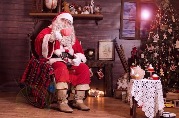 Père noël assis sur une chaise berçante au coin du feu et applaudit avec une grande tasse de lait dans la chambre décorée