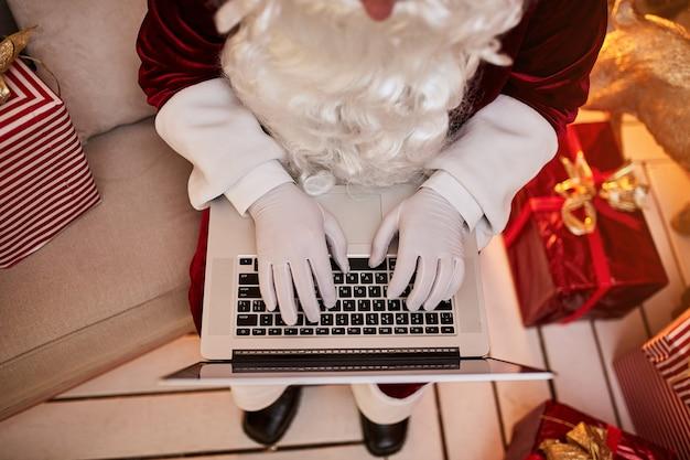 Le père noël assis chez lui et lisant des e-mails sur un ordinateur portable avec une demande de hristmas ou une liste de souhaits près de la cheminée et de l'arbre avec des cadeaux. nouvel an et joyeux noël, concept de joyeuses fêtes