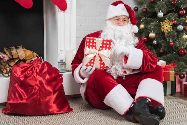 Père noël assis avec des coffrets cadeaux au sol