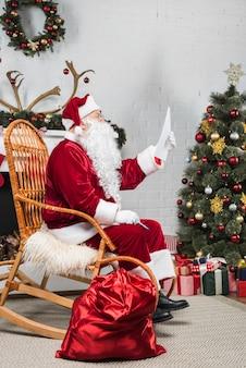 Père noël assis dans une bascule et lisant une liste de souhaits