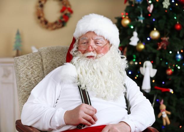 Père noël assis dans une chaise confortable près de la cheminée à la maison