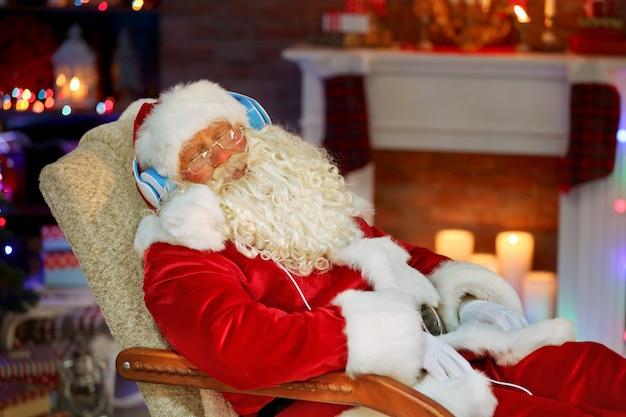 Père noël assis avec des écouteurs assis dans un fauteuil à bascule confortable à la maison