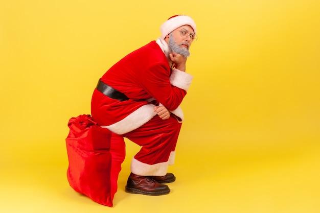 Père noël assis sur un grand sac rouge avec des cadeaux, attendant les vacances de noël pour féliciter.