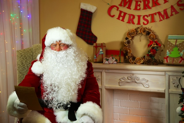 Père noël assis avec une liste de cadeaux dans une chaise confortable près de la cheminée à la maison