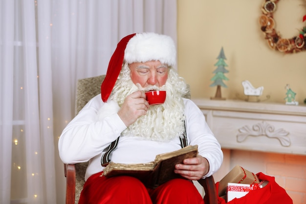 Père noël assis avec livre dans une chaise confortable près de la cheminée à la maison