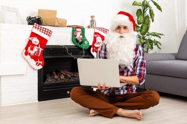 Père noël assis avec un ordinateur portable sur le fond de la cheminée