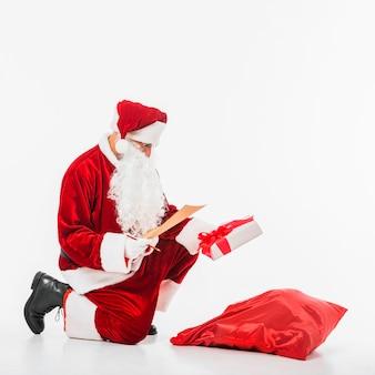 Père noël assis avec sac de cadeaux et liste d'enfants